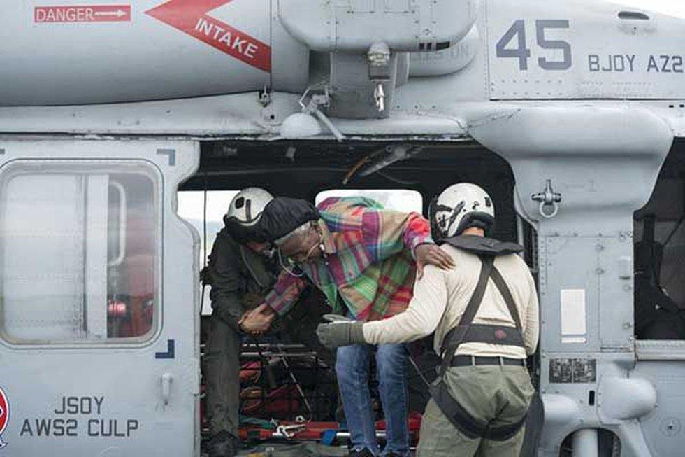 Members of the Navy help a woman during Hurricane Harvey. (Source: Dawne Gee)