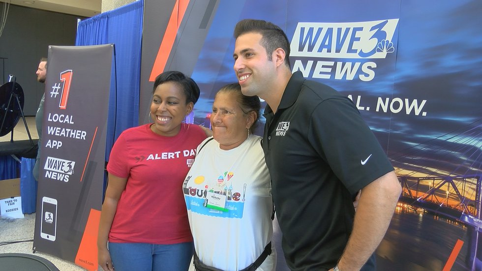Meteorologist Tawana Andrew and Sunrise anchor Brian Shlonsky posing with a WAVE 3 News viewer.