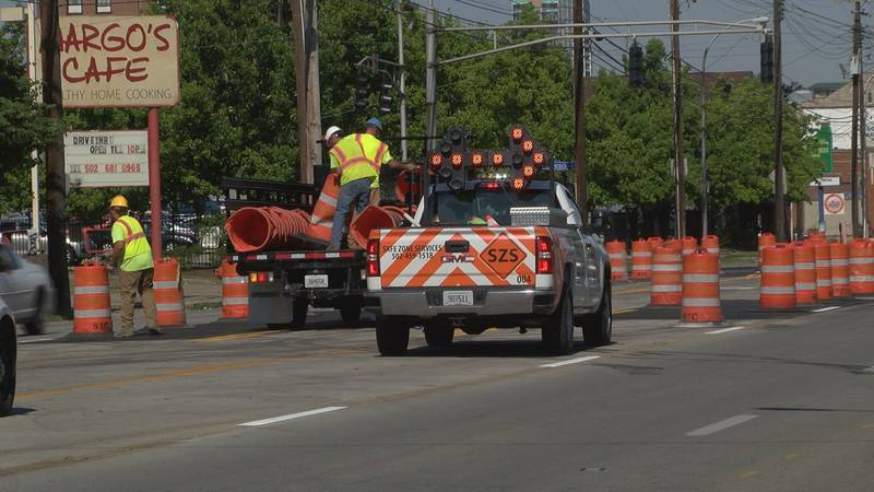Workers removed the orange traffic control barrels along E. Broadway after MSD crews finished...