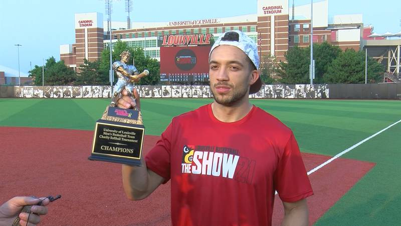 UofL guard Jarrod West holds up softball trophy after 11-8 win