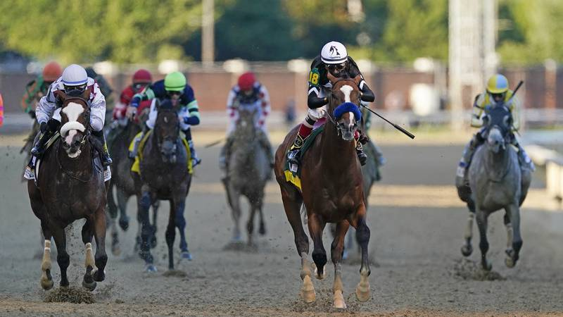Jockey John Velazquez rides Authentic, second from right, as they cross the finish line to win...