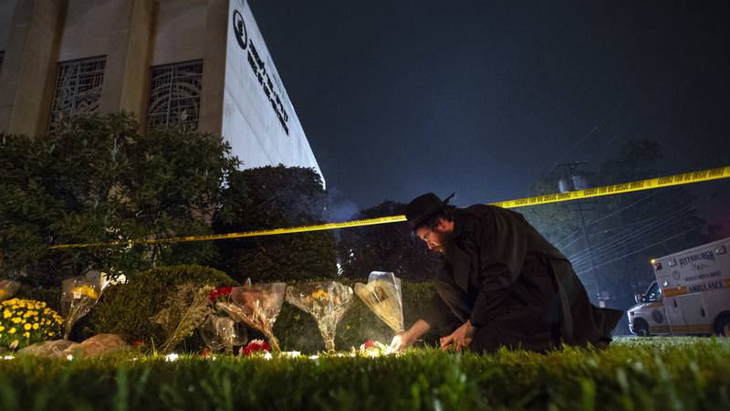 In this Oct. 27, 2018 photo, Rabbi Eli Wilansky lights a candle after a mass shooting at Tree...