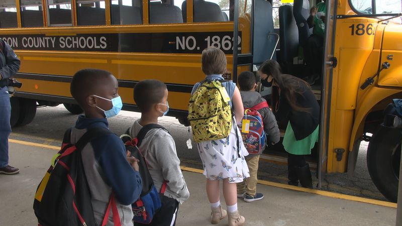Students get back on the bus after their first day back at school for in-person instruction in...