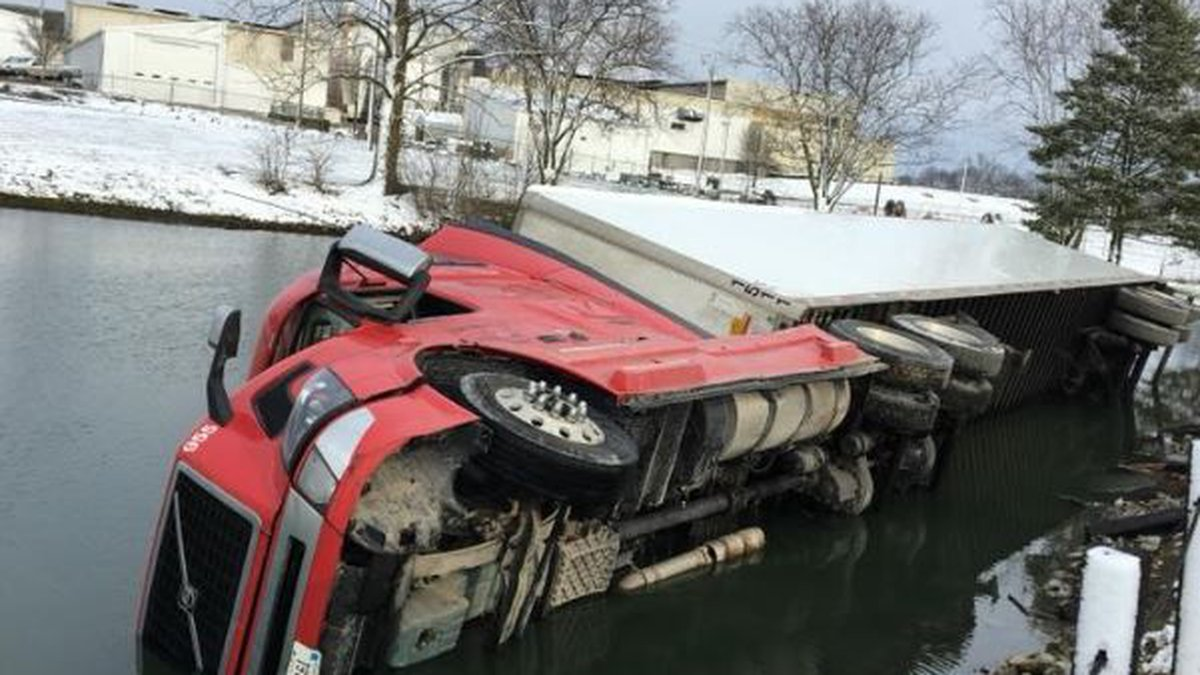 A tractor-trailer hauling steel slipped off an area roadway and landed on its side in a pond in...