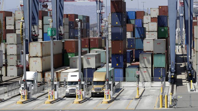 FILE- In this Aug. 22, 2018, file photo cargo is unload from trucks at the Port of Long Beach...