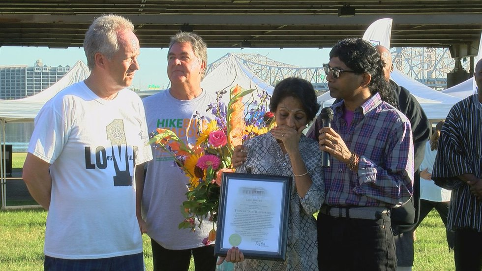 Mayor Greg Fischer presented a plaque to Sam Rangaswamy's family during the Hike, Bike and...