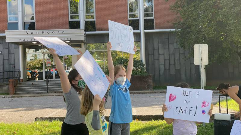 """Students held signs saying """"Keep me safe"""" and """"Wear your mask."""""""