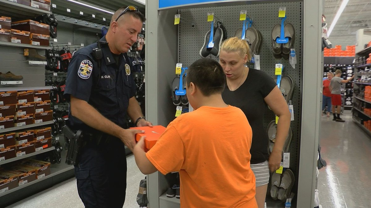 An officer helped a student find the perfect pair of shoes for the upcoming school year.