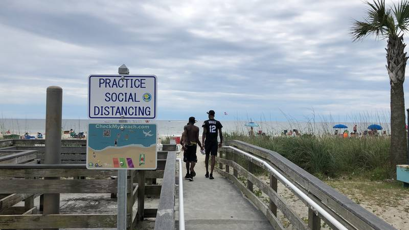 A sign in Myrtle Beach, S.C., Thursday, June 18, 2020, asks people to maintain social...