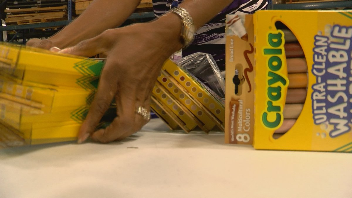 Volunteers pack markers and crayons for New Albany Floyd county Schools Colors of the World...