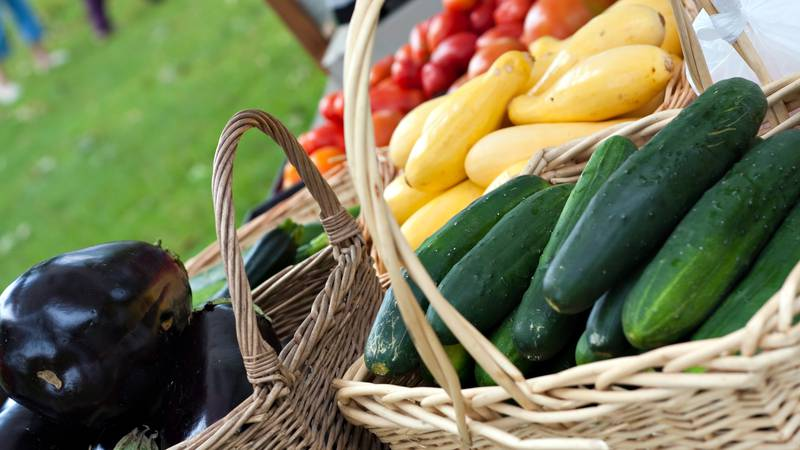 Farmers market baskets on a table full with fresh organic produce. Shallow depth of field.