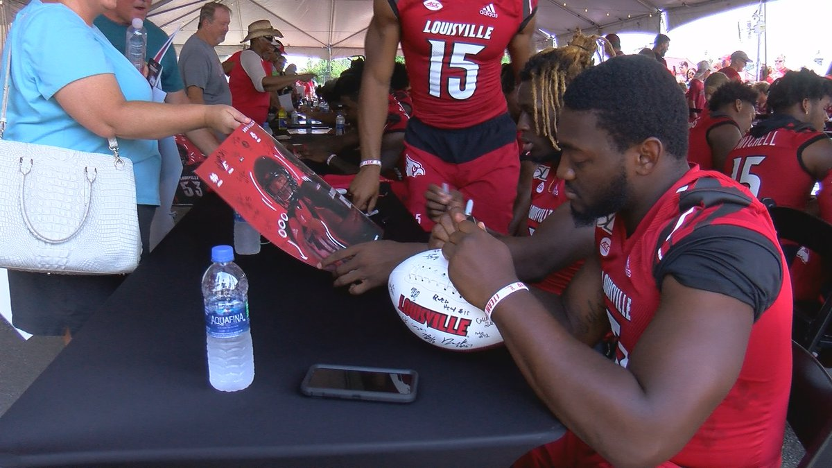 UofL Football players signed footballs, posters and other memorabilia for fans.