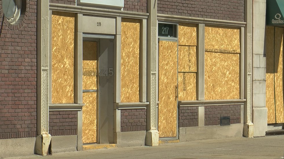 Windows and doors of Louisville businesses are covered by boards ahead of planned protests this...