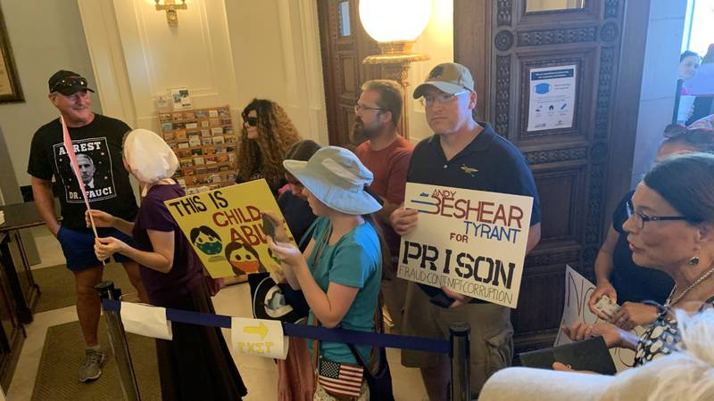 Anti-mask demonstrators carried signs and chanted their support for eliminating mask mandates...