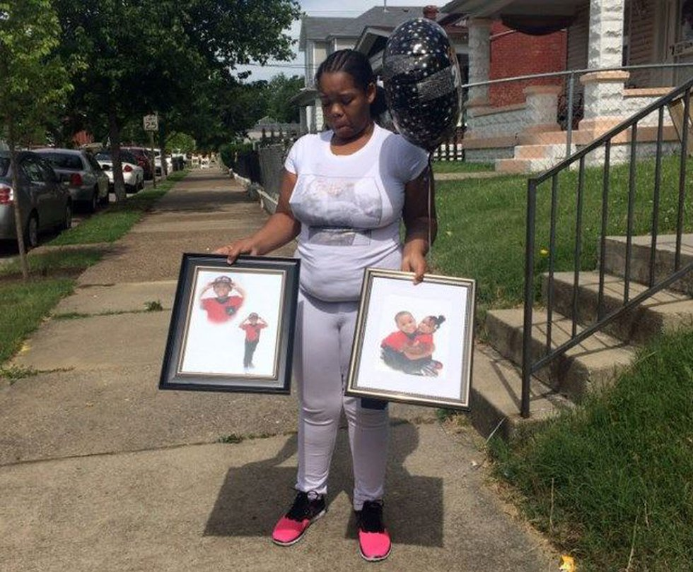 Micheshia Norment displays photos of her son Dequante. (Source: Maira Ansari/WAVE 3 News)