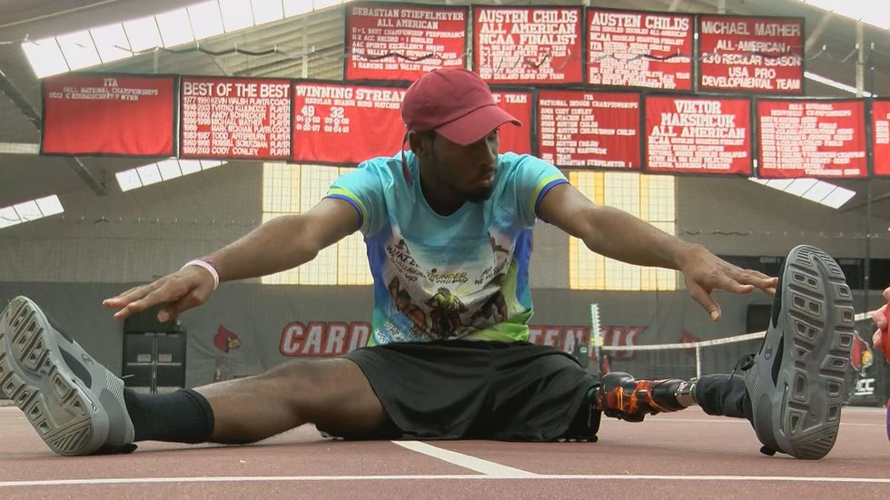 Dionte Foster stretches out his legs on the UofL tennis court.