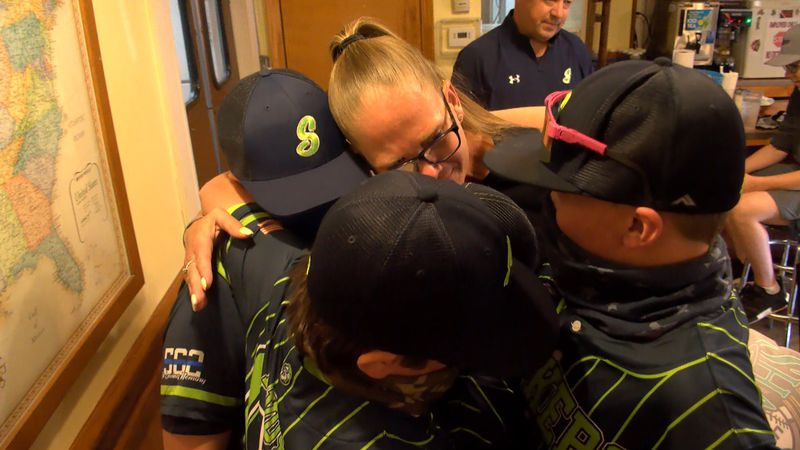 Members of the Indiana Strikers embrace TeJuan Johnson's wife as they present her with trophies...