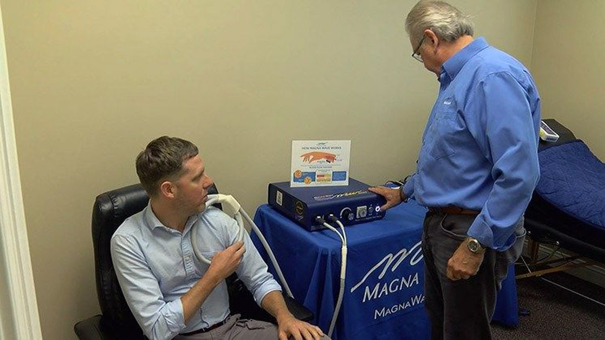 Pat Ziemer treats a patient with MAGNA Wave therapy. (Source: WAVE 3 News)