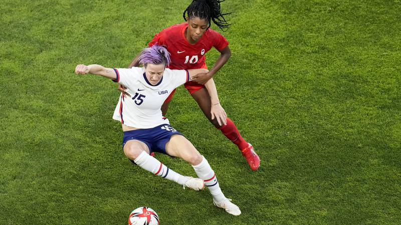 United States' Megan Rapinoe, left, and Canada's Ashley Lawrence battle for the ball during a...