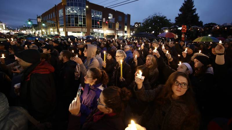 People hold candles as they gather for a vigil in the aftermath of a deadly shooting at the...