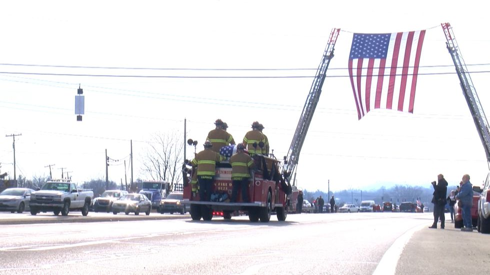 After the funeral ceremony, Fire Chief Rob Orkies' casket was led in a procession around...