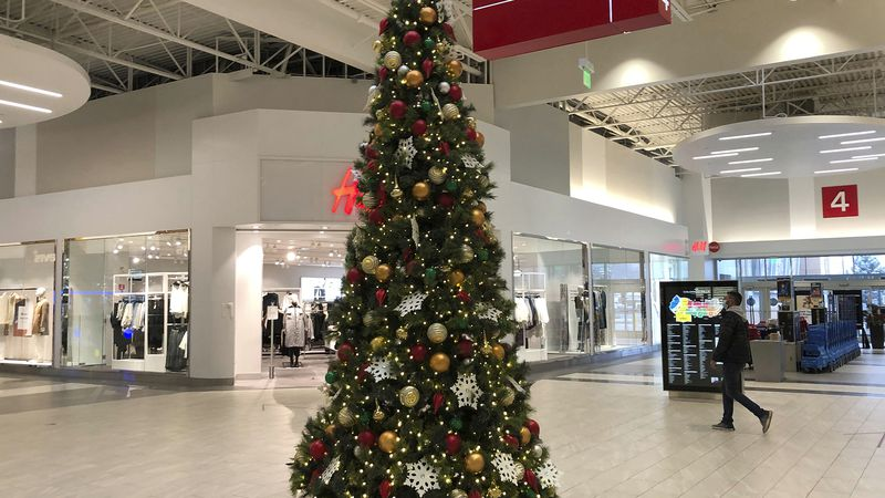 A lone shopper walks past the Christmas tree set up in an outlet mall Monday, Nov. 9, 2020, in...