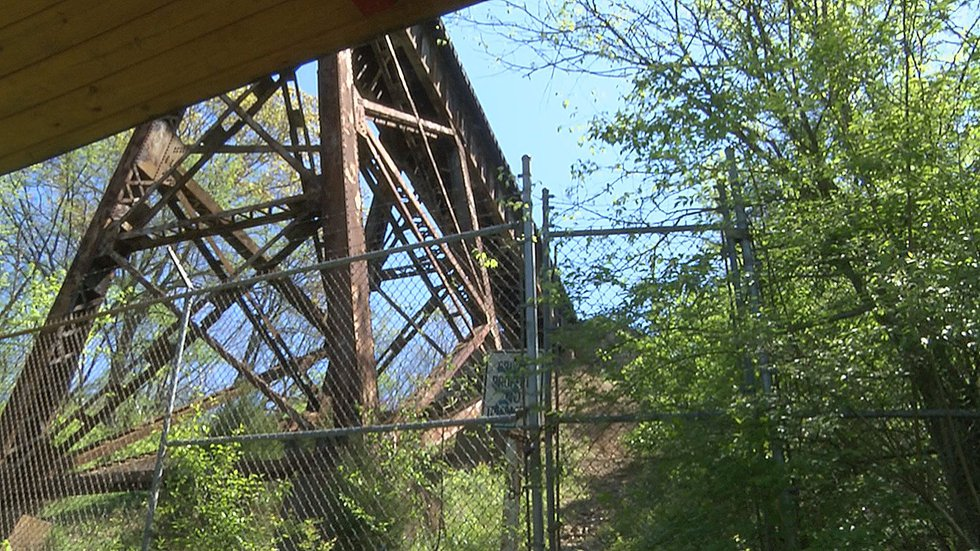 There are fences and warning signs at the bottom of the trestle warning people the tracks are...