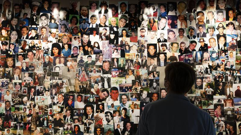 Désirée Bouchat, a survivor of the 9/11 attacks on the World Trade Center, looks at photos of...