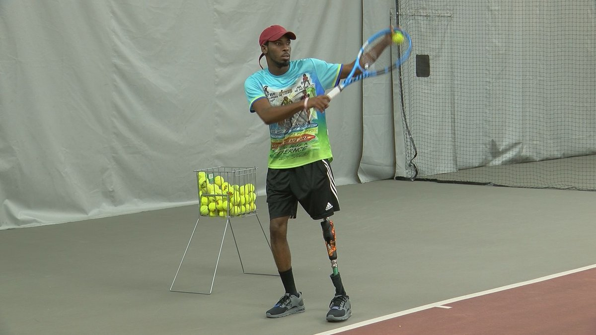 Foster gets ready to serve a ball on the court using his new leg.