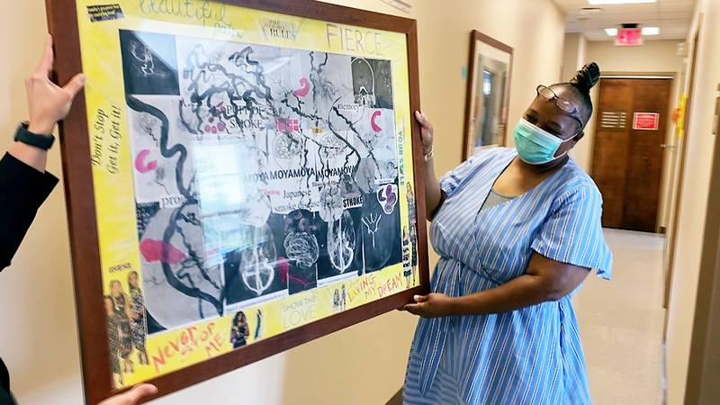 Trisha Moore received a piece of art on Monday from the Frazier Rehabilitation Institute...